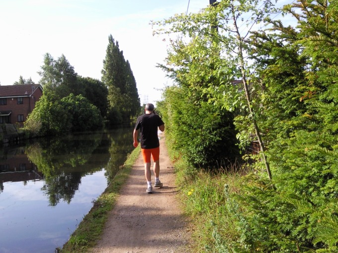 man in orange pants walking along the canal onsunday morning
